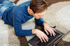 Young man lying on the floor and using laptop Stock Photo