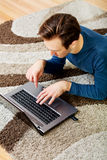 Young man lying on the floor and using laptop Stock Images