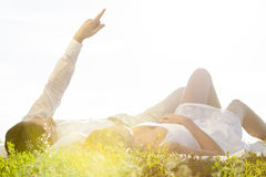 Young man lying with girlfriend while pointing against clear sky Stock Photo