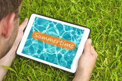 Young man lying on grass in garden with tablet device looking at water background with word & x22;Summertime& x22; written on it.  Stock Photography