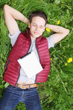 Young man. Lying in the grass with iPads Stock Image