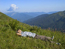 Young man lying on grass in mountains in sun Stock Image