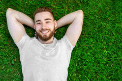 Young man lying on the grass in park Stock Images
