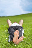 Young man lying on grass in park Royalty Free Stock Photography