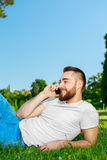Young man lying on the grass in park with phone Stock Photography