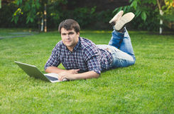 Young man lying on grass at park and working with laptop Royalty Free Stock Photography