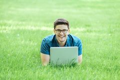 Young man lying on grass and using laptop Royalty Free Stock Image