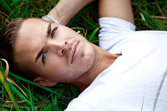 Young man lying on green gras. Beautiful young man lying on green gras Royalty Free Stock Photography