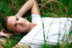 Young man lying on green gras. Beautiful young man lying on green gras Royalty Free Stock Photo