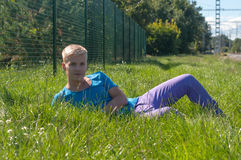Young man lying on the green grass. Young an in blue t-shirt lying on the grass Royalty Free Stock Images