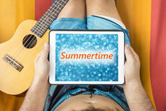 Young man lying on a hammock with tablet device looking at blurred blue background with word & x22;Summertime& x22; written on it Stock Photos