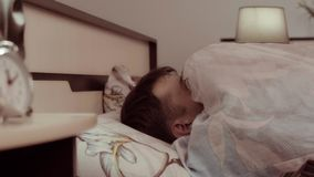 Young man lying in his bed is frightened and slowly pulling the blanket on himself stock footage