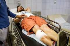 Young man lying in a hospital bed in the building of ambulance of a doctor with an injured leg bloodied and temporary bandaging royalty free stock images