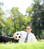 Young man lying in park and holding a football Royalty Free Stock Photos