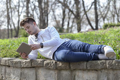 Young man lying in the park, holding a tablet in his hands and e. Young man lying in the park looking at the tablet and enjoy the beautiful day. Selective focus Royalty Free Stock Images