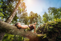 Young man lying and relaxing in the forest. Young man lying on a tree trunk, relaxing in the forest. Summer activity and freedom concept. Low angle perspective Royalty Free Stock Images