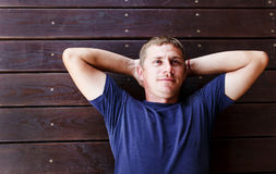 Young man lying and relaxing on wooden deck outdoor. royalty free stock photos