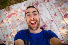 Young man lying on a sheet in the park and taking selfie picture Stock Images