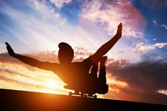 Young man lying on skateboard at sunset. Stock Image