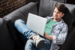 Young man lying on sofa and using laptop at home, small business people concept. Serious young man lying on sofa and using laptop at home, small business people Stock Photography
