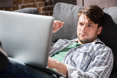 Young man lying on sofa and using laptop, small business people concept. Handsome young man lying on sofa and using laptop, small business people concept Royalty Free Stock Images
