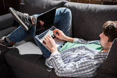 Young man lying on sofa and using laptop, small business people concept. Serious young man lying on sofa and using laptop, small business people concept Royalty Free Stock Image