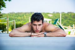 Young Man Lying on Stomach on Sun Deck. Attractive Young Dark Haired Man Lying on Stomach on Sun Deck with Lounge Chairs, Outdoors on Sunny Day with Forest in Stock Photo