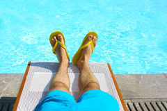 Young man lying on sunbed near pool. Summer vacation and travel. Concept Stock Photo