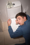 Young man lying on toilet seat. Drug addict kneeling over toilet seat with dollars Stock Photography