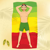 Young man lying on a towel at the beach in the form of a flag of Ethiopia Stock Photography