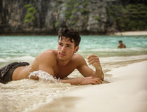 Young man lying on a tropical beach. Half body shot of a handsome young man laying on a tropical beach in Phuket Island, Thailand, shirtless wearing boxer shorts Stock Image