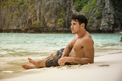 Young man lying on a tropical beach Royalty Free Stock Images
