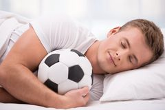 Young man lying under a blanket with soft ball Royalty Free Stock Image