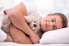 Young man lying under a blanket with teddy bear Stock Photo