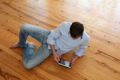 Young man lying on wooden floor and using tablet Royalty Free Stock Image