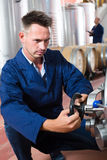 Young man machinery operator working in winery Royalty Free Stock Image