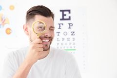 Young man with magnifier. Visiting ophthalmologist stock images