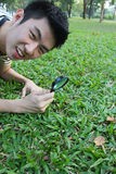 Young man with magnify glass. Young man with magnify glass in the park stock photo