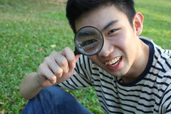 Young man with magnify glass. Young man with magnify glass in the park stock photography