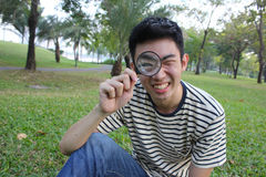 Young man with magnify glass. Young man with magnify glass in the park royalty free stock photos