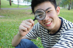 Young man with magnify glass. In the park, spring time Stock Images