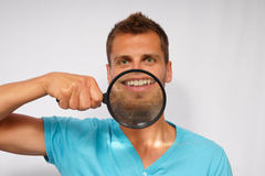 Young man with a magnifying magnifier Stock Photography