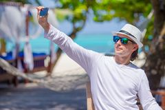 Young man make a photo on cell phone at tropical Stock Photos