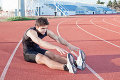 A young man makes an athlete stretching. Royalty Free Stock Image