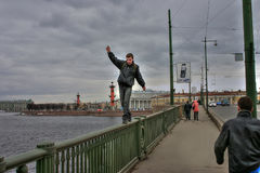 Young man makes life threatening walk on parapet of bridge. Royalty Free Stock Image
