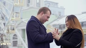Young man makes marriage proposal to beautiful woman in the amusement park. Young man makes a marriage proposal to his girlfriend standing at the background of stock footage