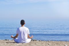 Young man makes meditation in lotus pose on sea / ocean beach, harmony and contemplation. Boy practicing yoga at sea resort at her. Vacation. Life style. Young Royalty Free Stock Photos