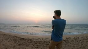 Young man makes a photo during sunset. Caucasian boy is making photo at the Srilankian sea stock video footage