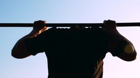 A young man makes pull-ups on the horizontal bar. stock video