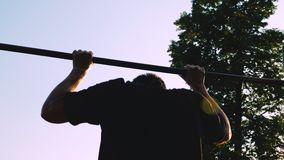 A young man makes pull-ups on the horizontal bar. Silhouette of a man against the background of dark blue cloudy sky stock video footage